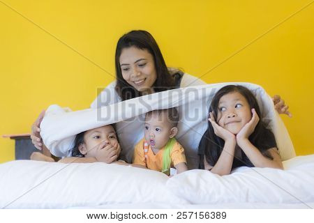 Babysitting Playing With Three Playful Kids Carrying On The Bed; Widow Young Woman And Child Are Enj