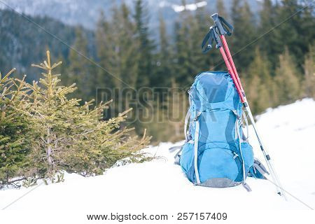 Backpack On The Background Of Snow-capped Mountains And Blue Sky. A Backpack On The Snow. Active Lif