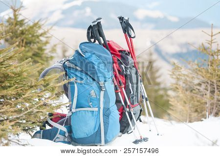 Two Backpacks In The Background Of Snow-capped Mountains And Blue Sky. A Backpack On The Snow. Activ