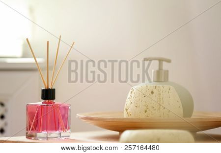 Aromatic reed air freshener and toiletries on table indoors poster