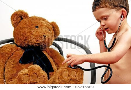 Young boy using stethoscope on big bear