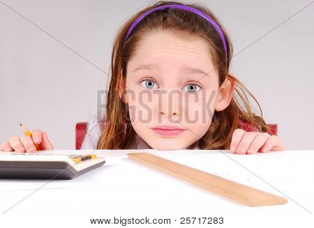 Cute young girl working on math homework at desk