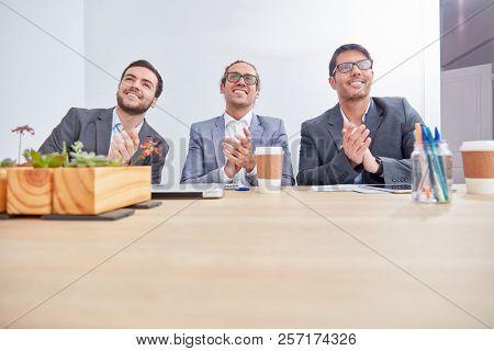 Three business men applaud in a seminar or seminar