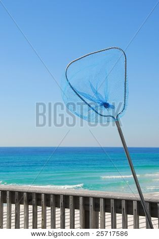 Blue fishing net on pier with beautiful ocean in background