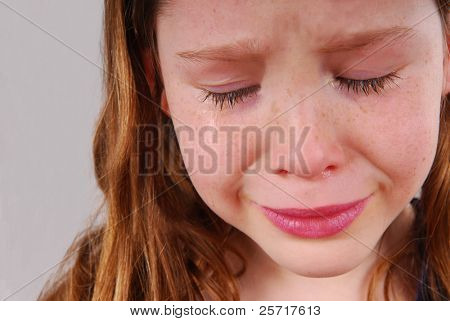 Young girl upset, crying with tears
