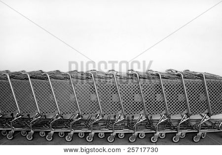 Row of shopping carts parked against a wall