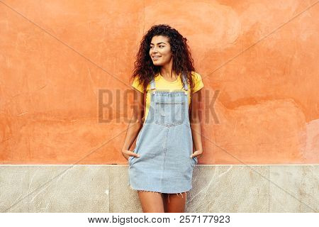 Smiling Arab Girl With Black Curly Hairstyle Looking Left Side. African Female In Casual Clothes In