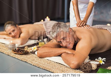 Mature couple in spa salon getting body massage and looking at camera. Senior man and beautiful woman relaxing at wellness center during beauty treatment. Mature couple lying on front at luxury spa.
