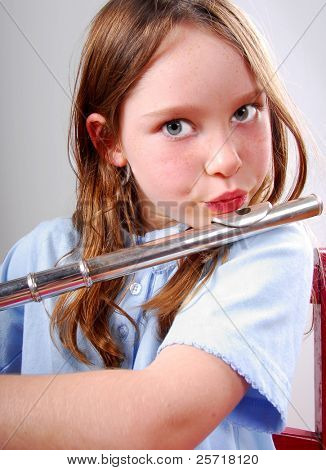 Cute young girl playing flute on chair