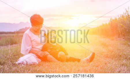 Grandmother, Daughter And A Dog With Happy Family Enjoying Life Together At Meadow; Light And Lens F