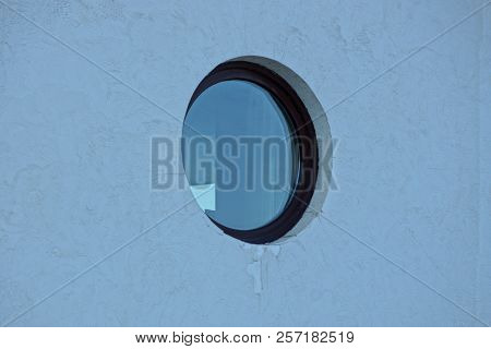 One Round Brown Window On A Gray Concrete Wall