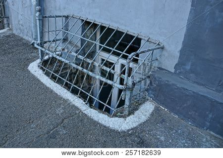 The Cellar Window Behind The Bars Of Steel Bars On The Gray Wall Near The Asphalt On The Street