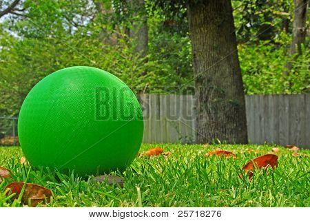 Bright green kickball on grass in summer yard