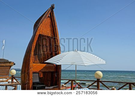 Part Of A Brown Wooden Boat And A White Umbrella On The Beach On A Background Of The Sky And The Sea