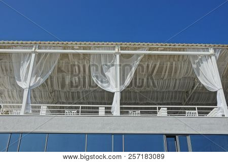 Part Of A White Outdoor Terrace With A Balcony And Curtains Against The Sky