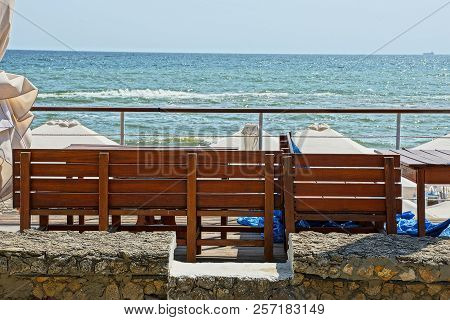 Brown Wooden Bench Against The Blue Sky And Sea Waves