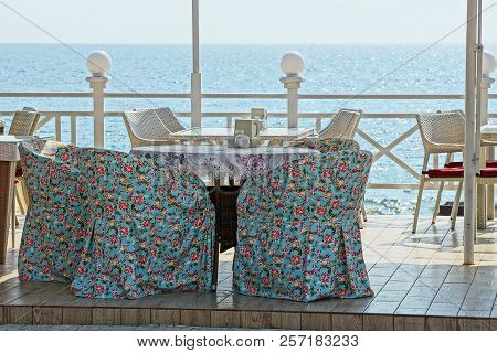 Colored Armchairs And A Table On The Outdoor Terrace Of A Summer Restaurant Against The Sky And The