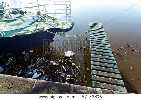 Water Pollution. Plastic Bottles, Packages, Trash In River Near Yacht.