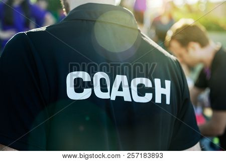 Sport Coach In Black Shirt With White Coach Text On The Back Standing Outdoor At A School Field, Wit