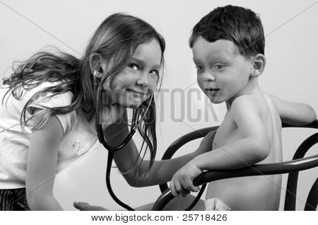 Cute girl using stethoscope to listen to boy's heart