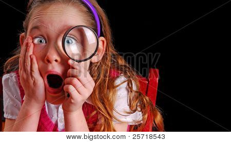 Young school girl looking through magnifying glass looking shocked at what she sees