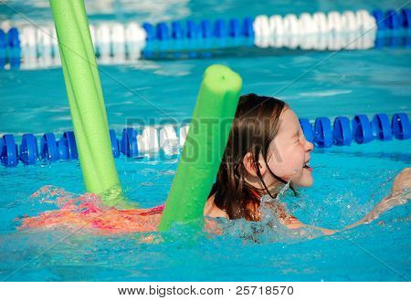 Young girl learning to swim using a styrofoam noodle in community swimming pool