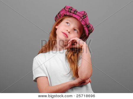 Young girl in pink plaid cap looking thoughtful