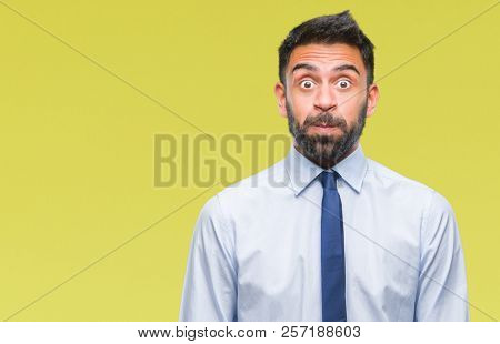 Adult hispanic business man over isolated background puffing cheeks with funny face. Mouth inflated with air, crazy expression.