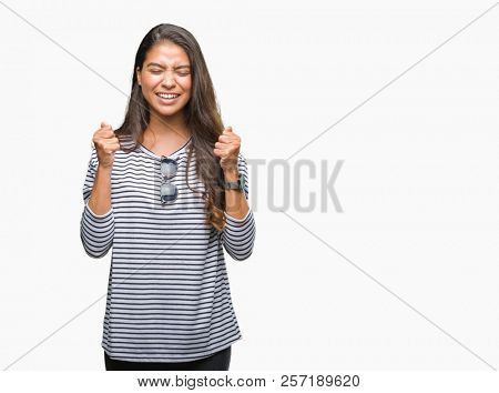 Young beautiful arab woman wearing sunglasses over isolated background excited for success with arms raised celebrating victory smiling. Winner concept.