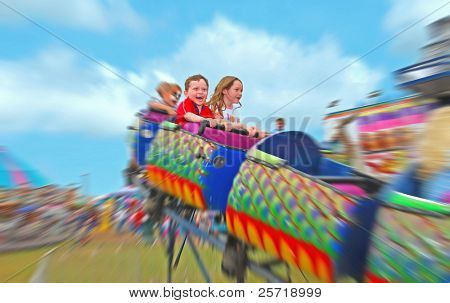 Happy kids on rollercoaster at amusement park