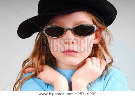 Young girl looking serious in sunglasses and black cap poster