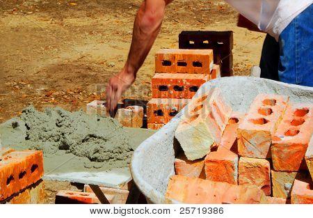 Fast moving brick master preparing cement for mortar