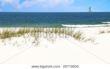 Pretty beach and ocean with sailboat and clouds in distance