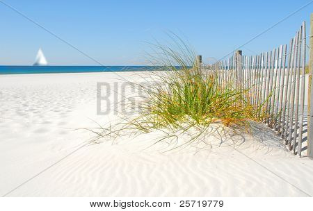 Beautiful sand dune fence by sea grass with sailboat on horizon