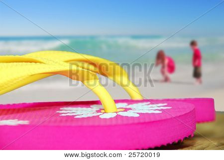Pretty flip flop sandals on dock next to ocean with children collecting shells in distance