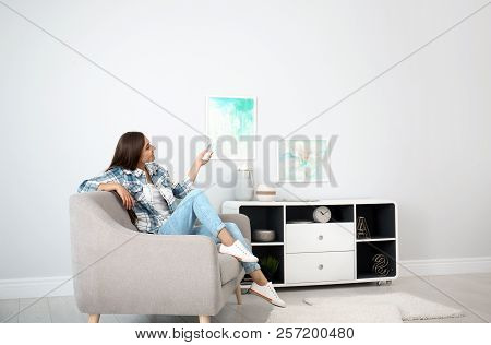 Young Woman With Air Conditioner Remote At Home