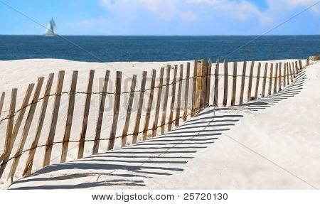 Pretty beach fence and ocean with sailboat and clouds in distance