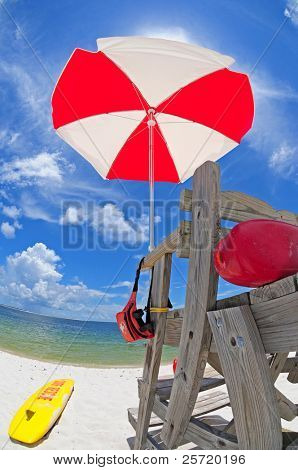 Life guard stand and umbrella under pretty sky by beach