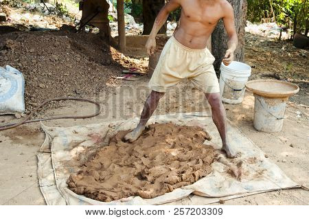 Man Stomping Clay For Pottery - Laos