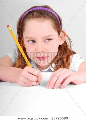 Young girl concentrating while working at desk on schoolwork