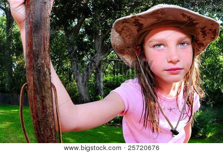 Young girl in pretty outdoors with walking stick for hike