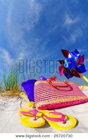 Pretty array of beach accessories on sand dune under blue sky