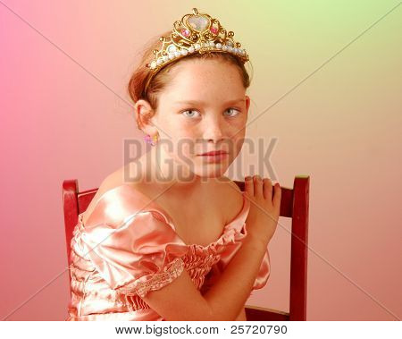 Young princess girl looking serious in chair
