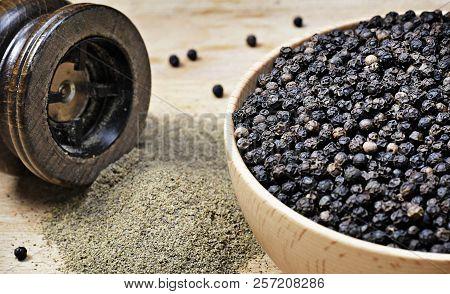 Black Peppercorns And Milled Pepper, Arrangement In A Wooden Bowl. Close Up Shot Of Black Pepper, Co