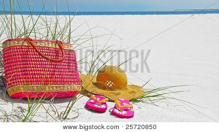 Pretty hat, beach bag, and flip flops on beach poster