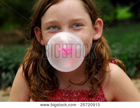 Young girl outside blowing bubble with gum