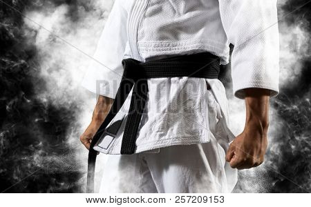 Guy poses in white kimono with black belt.  Japanese judo and sports concept