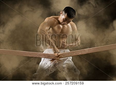 Determined karate man breaking with hand wooden board