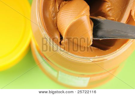 Peanut butter in jar with knife