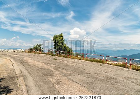 Uphill Asphalt Road With Cloudy Blue Sky With Mountains In The Background.